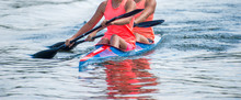 Two Young Woman Athletes On Rowing Kayak On Lake During Competition