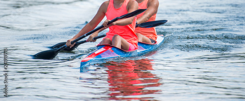 Fotografie, Obraz Two young woman athletes on rowing kayak on lake during competition