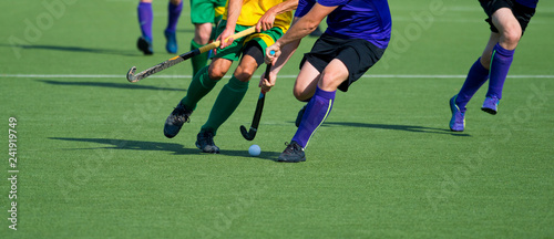 Fotografiet  Close up of two field hockey players, challenging eachother for the control and
