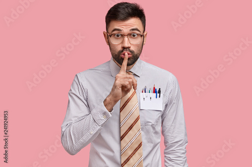 Photo  Male designer keeps finger on lips, dressed in formal clothes, has blank card wi