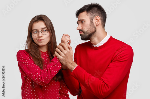 Fotografía  Desperate young Caucasian man holds hand of girlfriend, looks with miserable expression, asks for forgiveness, feels guilty