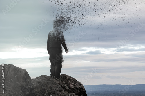 Fotografía  A concept photo of a hooded figure standing on a hill as his head  disintegrates into the air