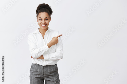 Studio shot of rich and sucessful good-looking office worker with dark skin and afro haircut, standing in suit and pointing right with index finger, holding hand crossed and smiling broadly