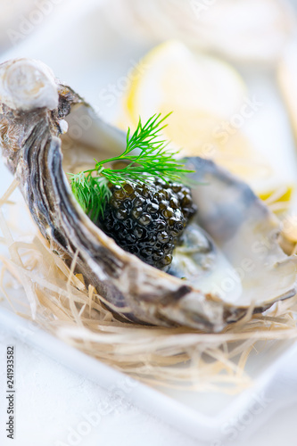 Fresh oysters with black caviar. Opened oysters with black sturgeon caviar. Gourmet food. Delicatessen. Vertical image
