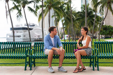 People City Lifestyle - Young Couple Talking On Park Bench Dating Or Going Out On Date Flirting Enjoying Beach Side Of Miami With Palm Trees. Florida Travel Destination. Asian Woman, Caucasian Man.