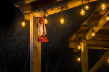 Red Metal Storm Lantern Hung Outside Rustic Log Cabin.