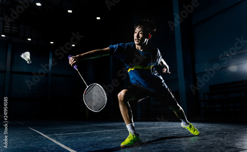 Photo Asian badminton player is hitting in court
