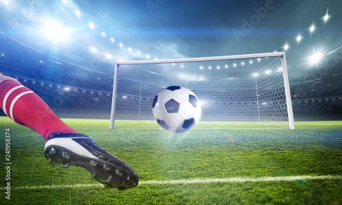 Football player kicks the ball on the stadium
