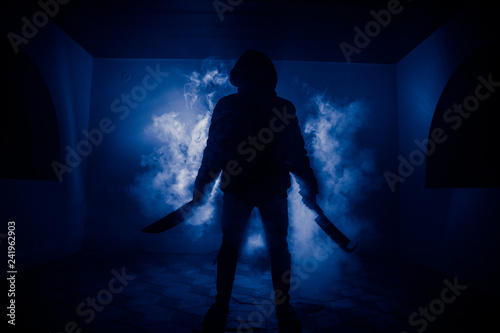 Fotomural  A dangerous hooded man standing in the dark and holding a knife