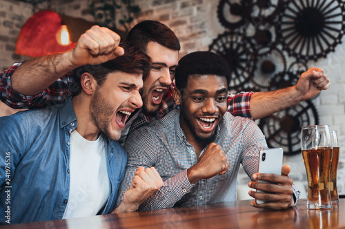 Men watching football on smartphone in bar - 241975536