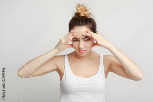Photo  Exhausted woman suffering from headache over gray background