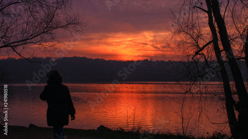 Poster Bordeaux Silhouette of a woman walking in front of a lake at sunset in winter with dramatic sky