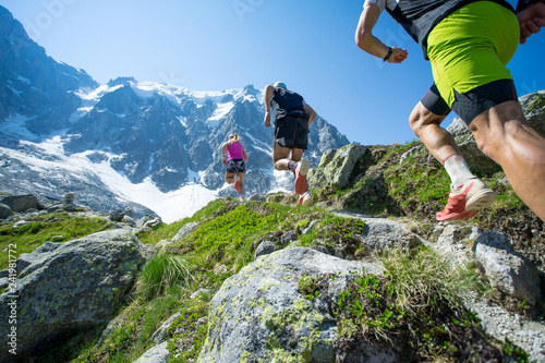 Three trail runners running up a steep trail towards the mountains in the Alps Wallpaper Mural