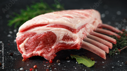 Fotografia raw fresh rack of lamb with green herbs.