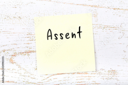 Yellow sticky note on wooden desk with handwritten text assent Canvas Print