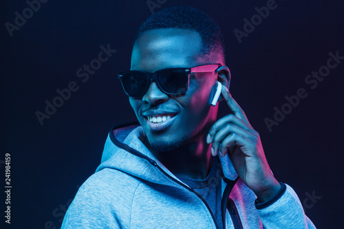 Foto  Neon portrait of young african man listening music with wireless earphones