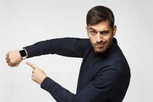 It's Time To Act! Man Pointing At Watch With Impatience As If Asking To Hurry Up, Isolated On Gray Background