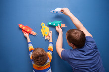 Father And Little Son Are Playing With Rocket Made Of Paper In The Home. Cheerful Time Together At Home. Preschool Child In Creativity In The Home.