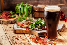 Concept Of Georgian Restaurant. A Glass Of Black Beer With Foam Stands On A Wooden Table, Next To It Is A Beer Snack, Dried Sausage, Basturma, Smoked Meat And Parsley With Dill.