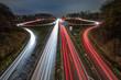 Autobahnausfahrt und Autobahnauffahrt bei Nacht mit Lichtstreifen