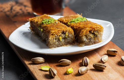 Cuadros en Lienzo Turkish famous dessert burma kadayif on plate with pistachio nuts near glass of