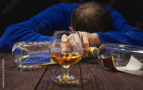 Photo Male alcoholic with glass of whiskey and bottle sleeping on table at night