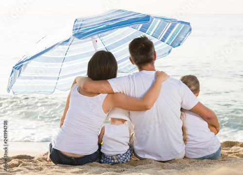 Fotografia  Young family and kids sitting with back forward