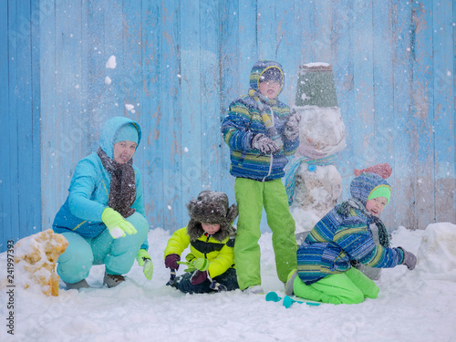 Mom And Three Happy Children In Winter Warm Clothes Make Snowmen And