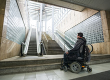 Rear View Of A Disabled Man On Wheelchair In Front Of Escalator And Staircase With Copy Space