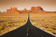 Straight road in Monument Valley at sunset, USA