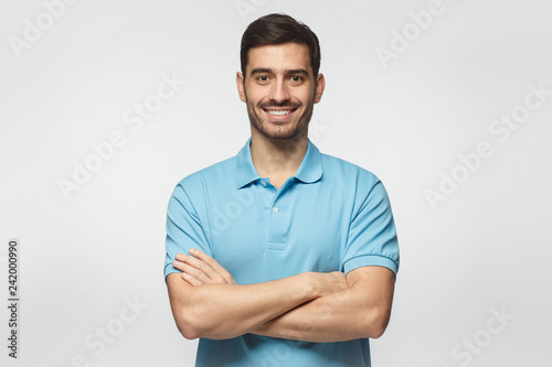 Fototapeta Smiling handsome man in blue polo shirt standing with crossed arms isolated on gray background obraz
