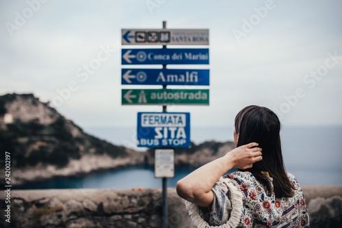 Ypung woman looking at sign table for direction.Wman on vacation in Italian coast.South cosat of Italy, Amalfi and Positano sightseeing