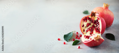 Ripe pomegranate fruit with green leaves on grey concrete background. Banner with copy space. Vegan, healthy diet concept