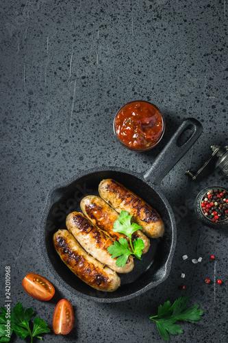 Fotografie, Obraz  Fried spicy  sausages in cast iron skillet on dark background