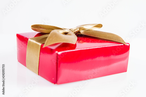 Fotografía  Wrapped gift with a golden ribbon on a white background
