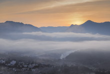 Top View Misty Morning Above Mae Hong Son City, View Of The Sea Of Mist Moving Above City Around With Mountain And Cloudy Sky Background, Sunrise At Wat Phra That Doi Kong Mu, Mae Hong Son Thailand.
