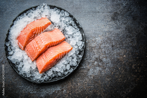 Foto Portioned raw salmon fillets in ice on plate - Top of view