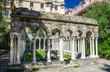 Ruins of Chiostro di Sant'Andrea monastery with columns and green plants around in historical centre of old european city Genoa Genova, Liguria, Italy