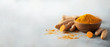 Turmeric powder in wooden bowl and fresh turmeric root on grey concrete background. Banner with copy space