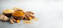 Turmeric And Giger Powder In Wooden Bowl And Fresh Turmeric Root On Grey Concrete Background. Banner With Copy Space