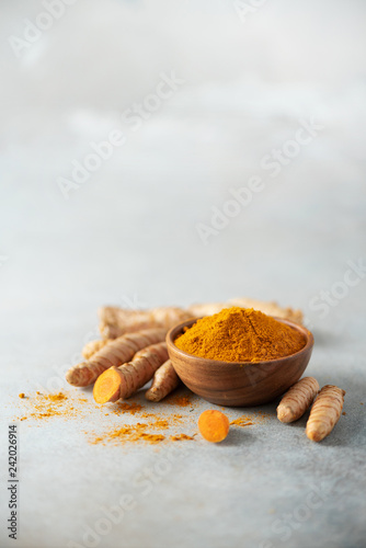 Fototapeta Turmeric powder in wooden bowl and fresh turmeric root on grey concrete background. Banner with copy space obraz