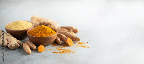 Fototapeta Turmeric and giger powder in wooden bowl and fresh turmeric root on grey concrete background. Banner with copy space obraz