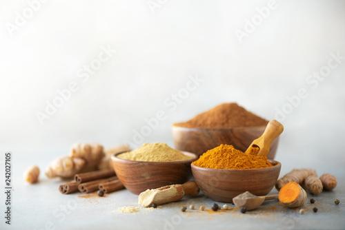 Fototapeta Ingredients for turmeric latte. Ground turmeric, curcuma root, cinnamon, ginger, black pepper on grey background. Spices for ayurvedic treatment. Alternative medicine concept obraz