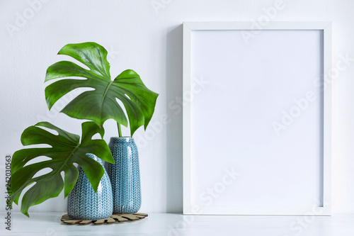 Poster Vegetal Modern and minimalistic composition of mock up photo frame with green tropical leafs in design vase. Stylish concept of mockup frame. White backgrounds wall.