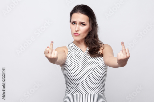 Photo  Portrait of angry young brunette woman with makeup and striped dress standing serious face and looking at camera and showing middle finger fuck sign