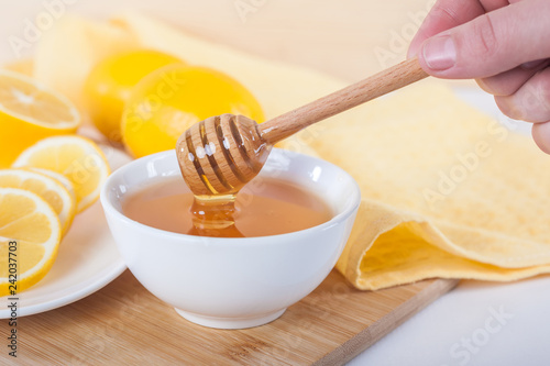 Photo  honey in a white ceramic bowl with honey dipper and lemon on a wooden kitchen bo