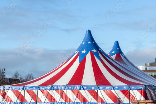 Fotografie, Obraz  Red and white circus tent topped with bleu starred cover against a sunny blue sk