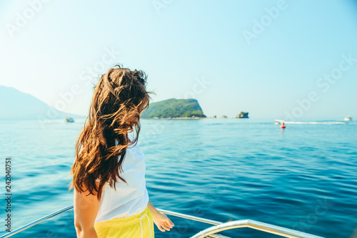 young pretty woman at boat nose sea with mountains and island on background Wallpaper Mural