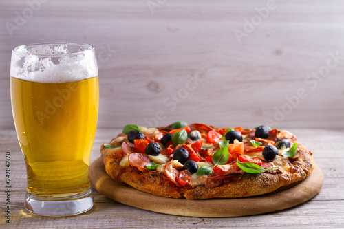 Foto op Canvas Bier / Cider Beer and pizza on wooden plate. Ale and snack. Horizontal