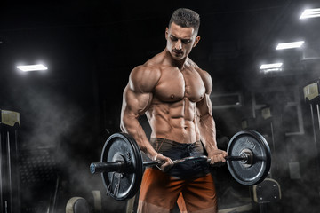 Fototapeta na wymiar Young handsome sexy man, athlete, bodybuilder, weightlifter, in a modern gym is covered with a dark background, doing exercises for the biceps using sporting goods - weights.